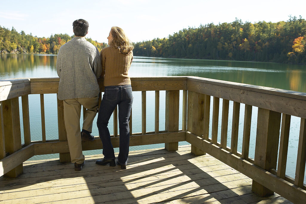 Couple relaxing on deck of their lakefront vacation home.