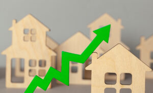 Wooden houses with arrow chart rising to represent market inflation