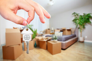 Home selling concept with house key and packed boxes.