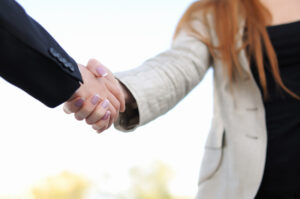 Real estate professional shaking hands with client.