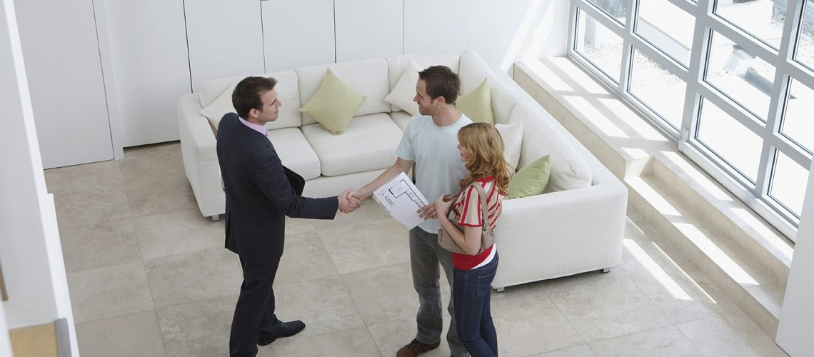 Couple meeting with real estate agent during home sale