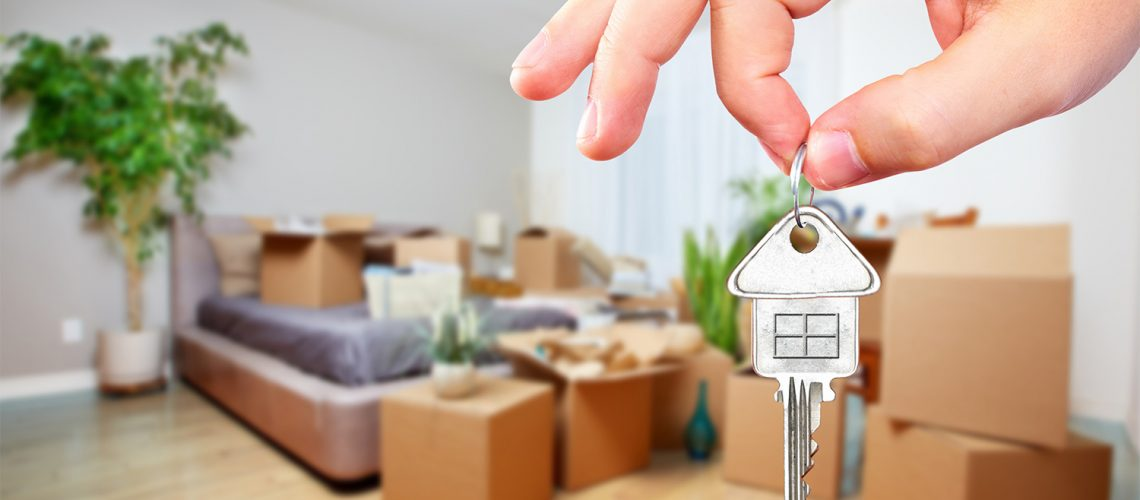 Home seller holding keys in front of packed home—moving in a seller's market concept
